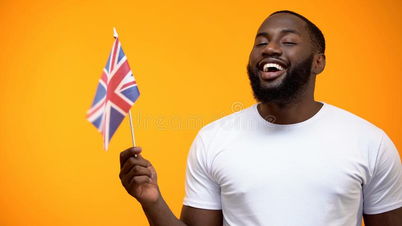 Hombre negro que sostiene la bandera brit?nica, amistad internacional, ayuda pol?tica imágenes de archivo libres de regalías