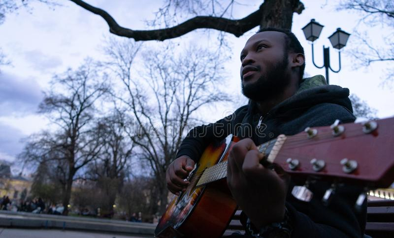 Hombre negro que toca una guitarra y que canta la sentada feliz en un banco de un parque fotografía de archivo libre de regalías