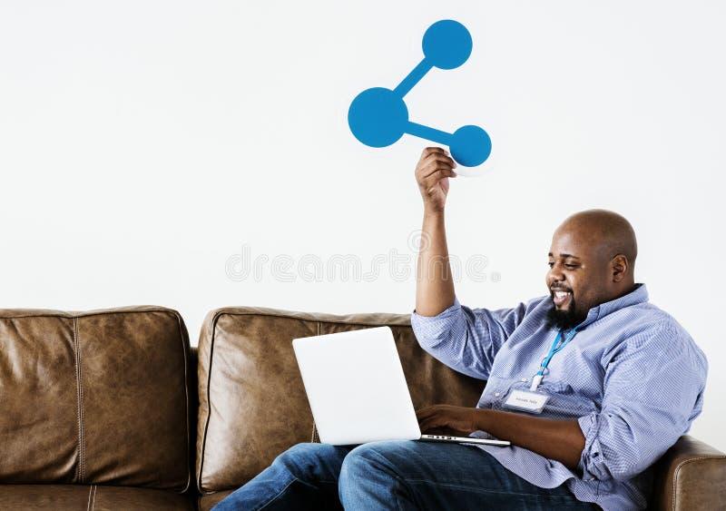 Hombre negro que trabaja en el ordenador portátil imagenes de archivo