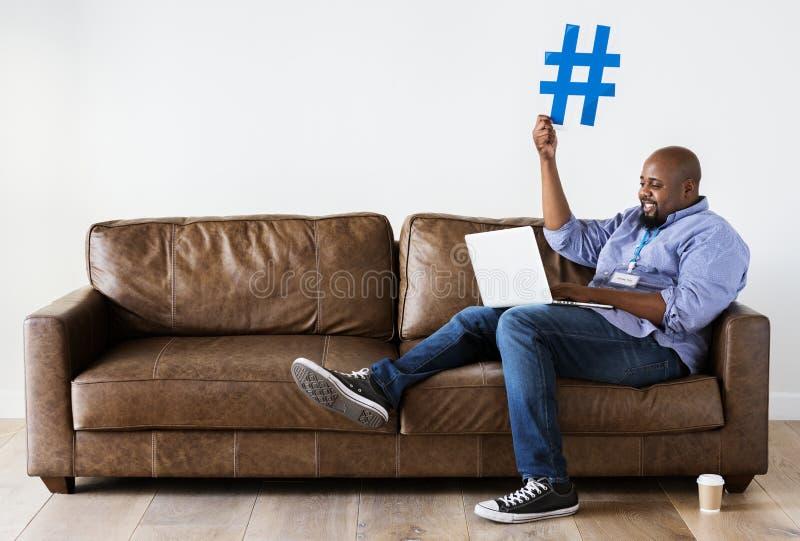 Hombre negro que trabaja en el ordenador portátil foto de archivo