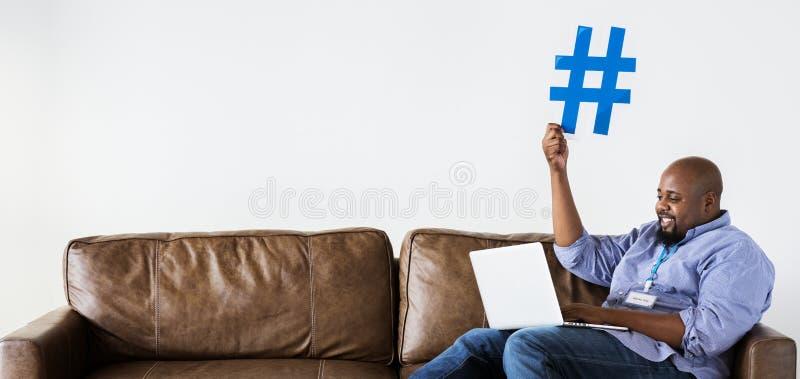 Hombre negro que trabaja en el ordenador portátil que lleva a cabo el icono del hashtag fotos de archivo libres de regalías