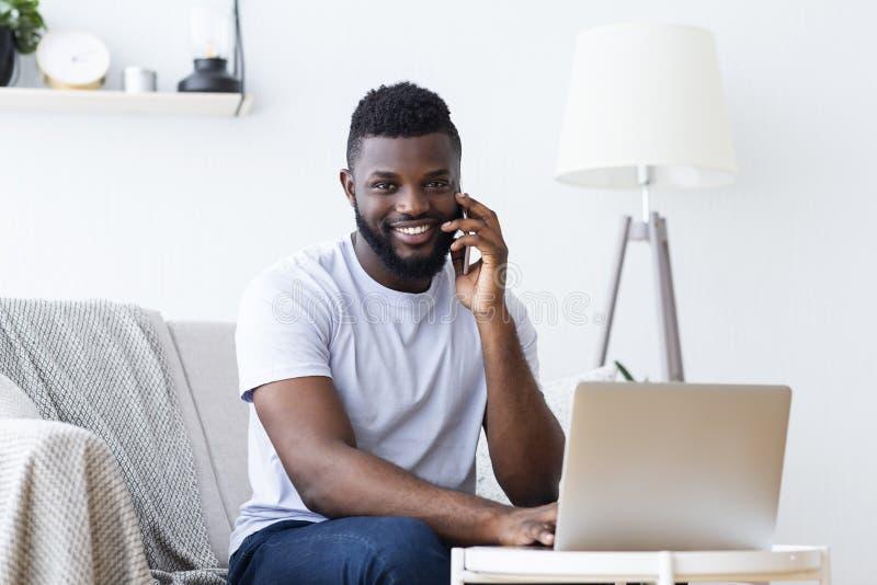 Hombre negro que trabaja en el ordenador portátil y la llamada imagen de archivo libre de regalías