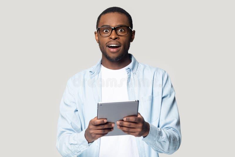 Hombre negro sorprendido con la tableta emocionada con buena oferta de la venta imagen de archivo