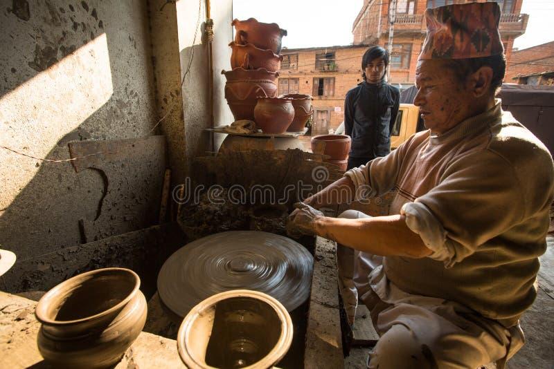 Hombre nepalés no identificado que trabaja en su taller de la cerámica foto de archivo libre de regalías