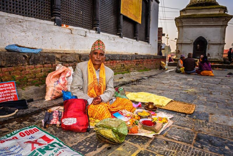 Hombre nepalés que vende las herramientas religiosas en el templo antiguo de Pashupatinath fotos de archivo