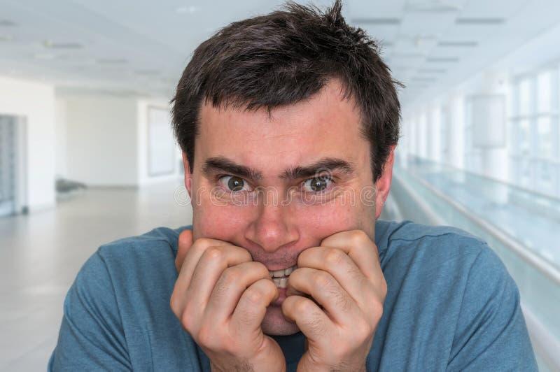 Hombre nervioso que muerde sus clavos - ataque de nervios imagenes de archivo