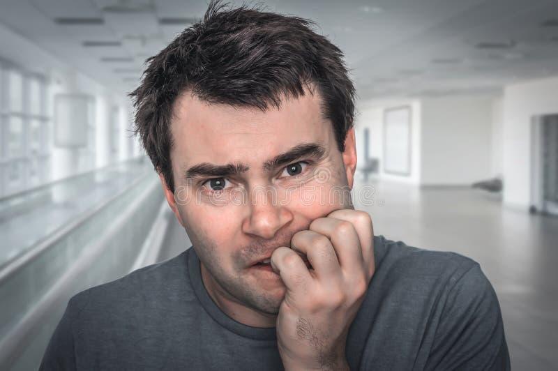 Hombre nervioso que muerde sus clavos - ataque de nervios fotografía de archivo