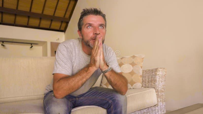 Hombre nervioso y emocionado atractivo joven que sienta en casa el partido de fútbol del sofá de la sala de estar o la película d fotografía de archivo libre de regalías
