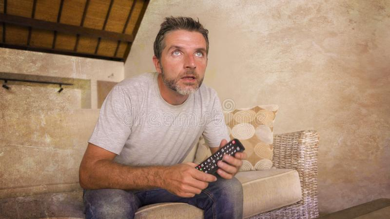 Hombre nervioso y emocionado atractivo joven que sienta en casa el sofá de la sala de estar que lleva a cabo el partido de fútbol imagen de archivo libre de regalías