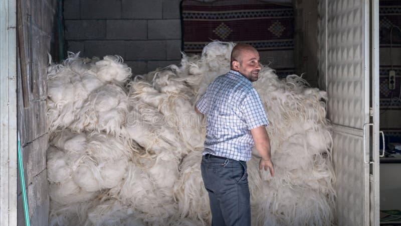 Hombre no identificado que vende las lanas en el suyo tienda en el bazar viejo histórico dentro de la ciudad vieja, Turquía de Ot foto de archivo