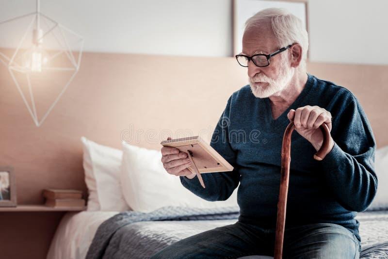 Hombre nostálgico triste que mira la foto imagen de archivo libre de regalías