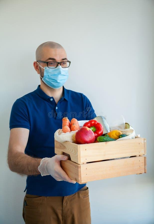 Hombre nutriente sosteniendo una caja llena de comida fotos de archivo libres de regalías