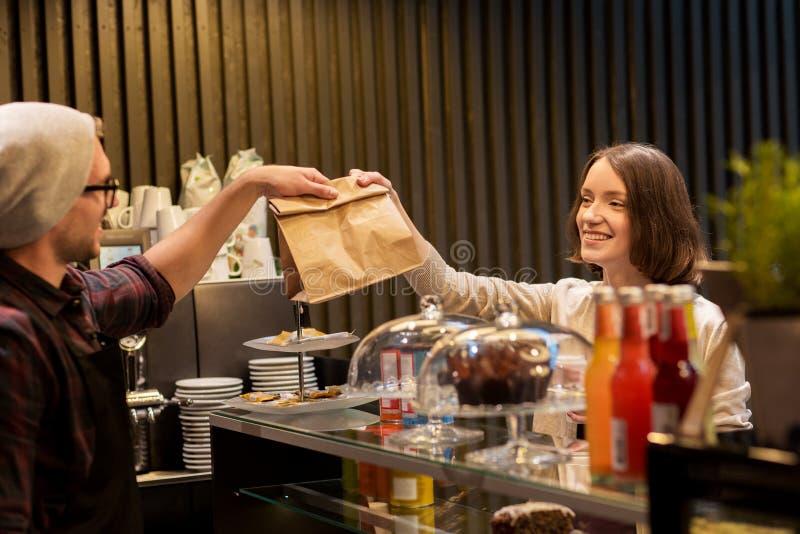 Hombre o camarero que da la bolsa de papel al cliente en el café foto de archivo libre de regalías