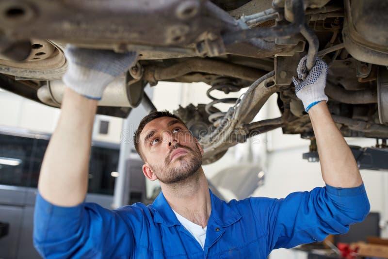 Hombre o forjador del mecánico que repara el coche en el taller imagen de archivo