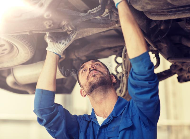 Hombre o forjador del mec?nico que repara el coche en el taller fotografía de archivo libre de regalías