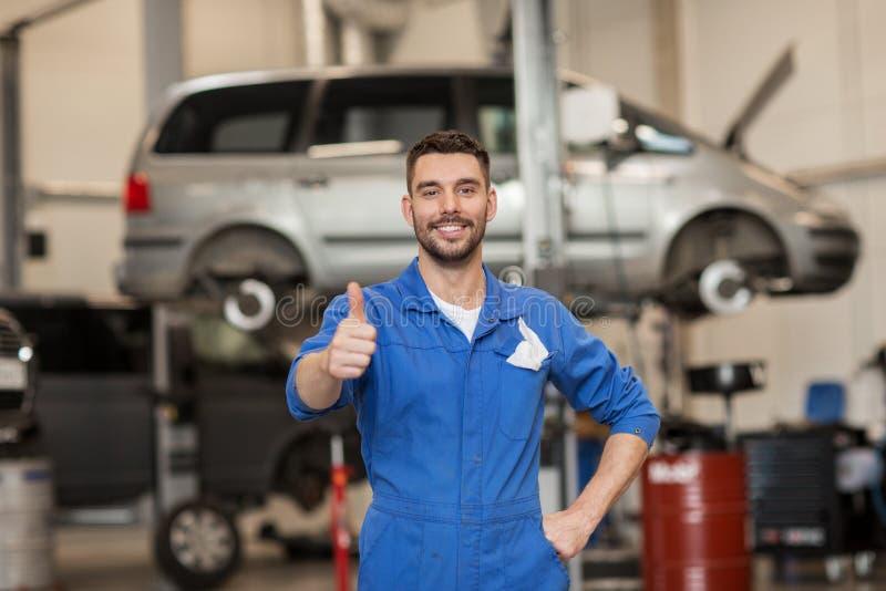 Hombre o forjador feliz del mecánico de automóviles en el taller del coche imagen de archivo libre de regalías