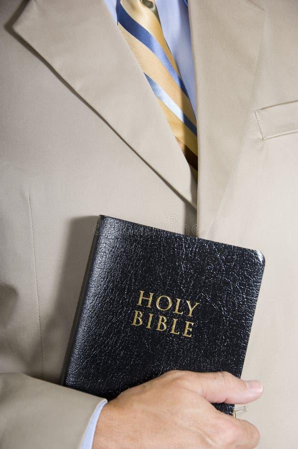 Hombre o predicador de negocios que sostiene una biblia de cuero fotos de archivo libres de regalías