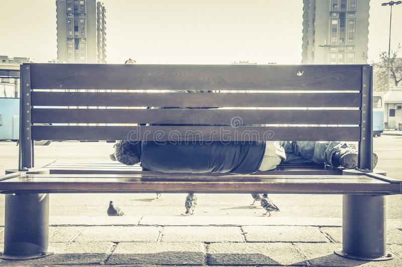Hombre o refugiado sin hogar pobre que duerme en el banco de madera en la calle urbana en la ciudad, concepto documental social fotografía de archivo