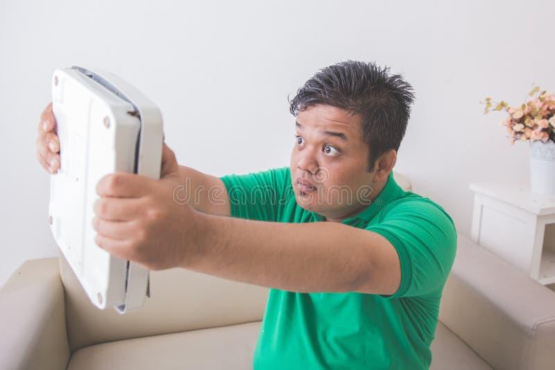 Hombre obeso chocado mientras que mira una escala del peso fotografía de archivo