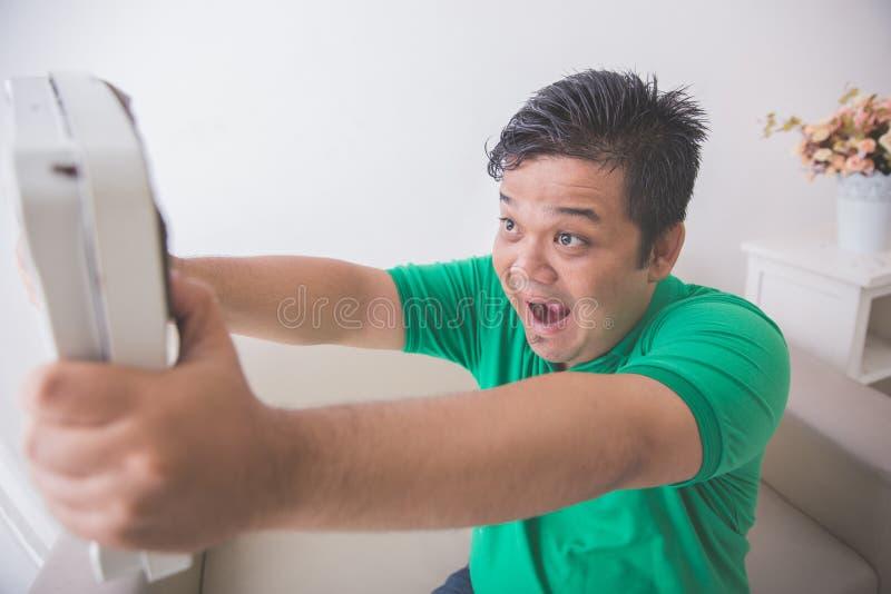 Hombre obeso chocado mientras que mira una escala del peso imagenes de archivo