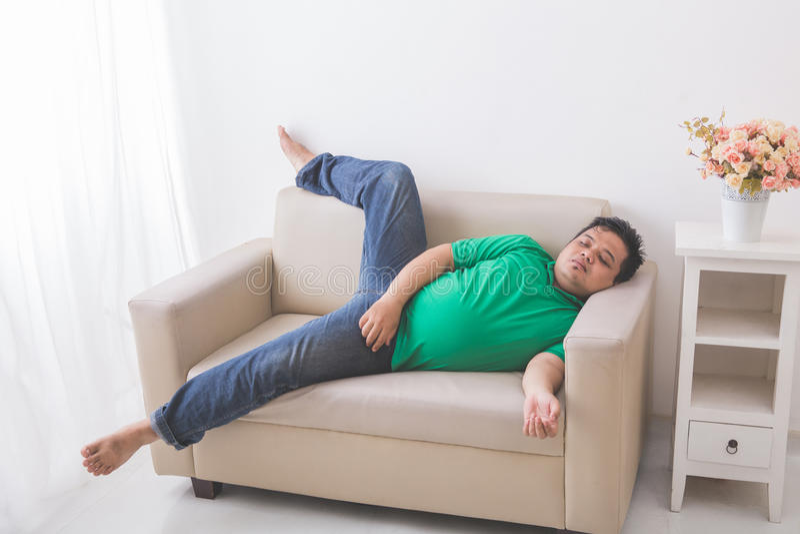 Hombre obeso gordo perezoso que duerme en el sofá fotografía de archivo