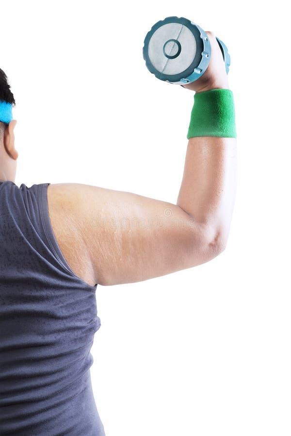 Hombre obeso que dobla los músculos con el barbell en estudio fotografía de archivo