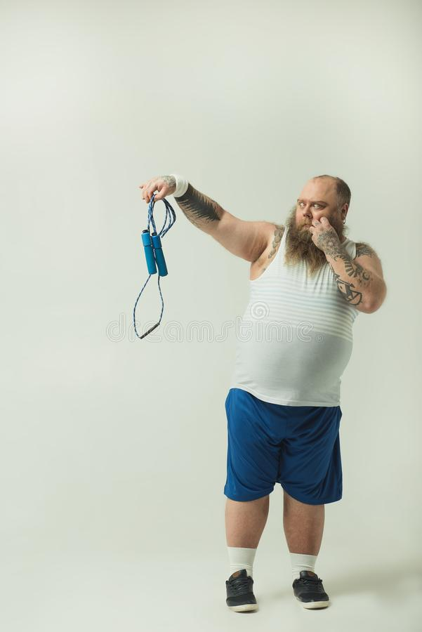 Hombre obeso que mira fijamente la saltar-cuerda con la aversión imágenes de archivo libres de regalías