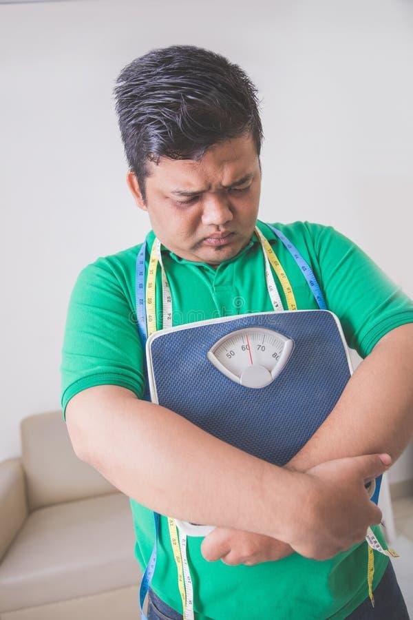 Hombre obeso triste que sostiene una escala del peso, pensando en su peso imagenes de archivo