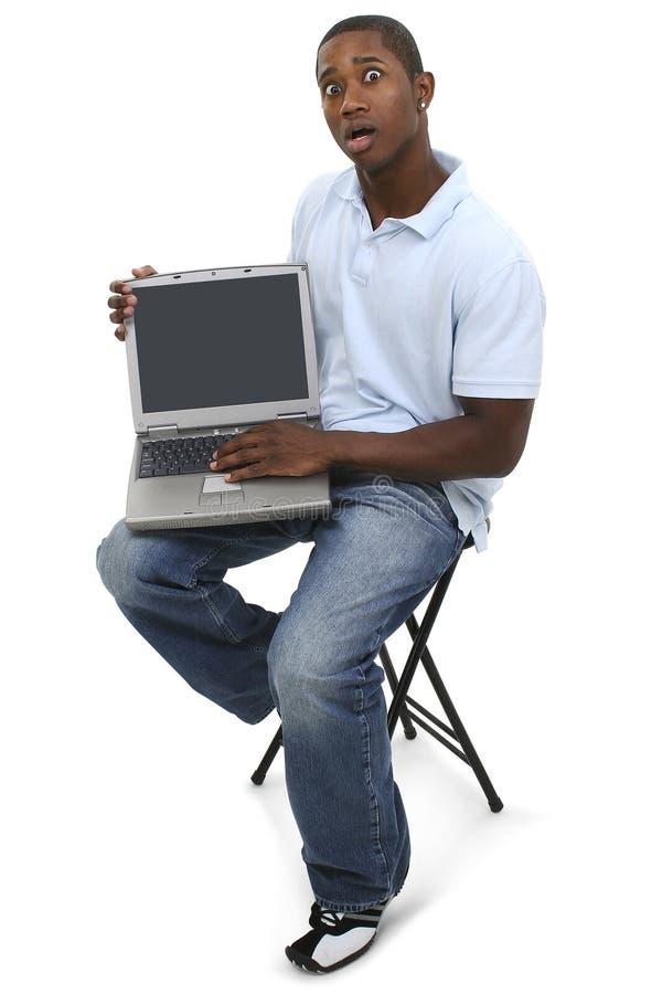 Hombre ocasional con el ordenador portátil y expresión dada una sacudida eléctrica en cara fotos de archivo