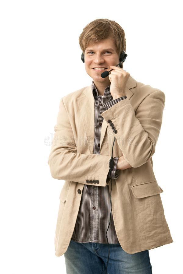 Hombre ocasional que se coloca que habla en el receptor de cabeza foto de archivo