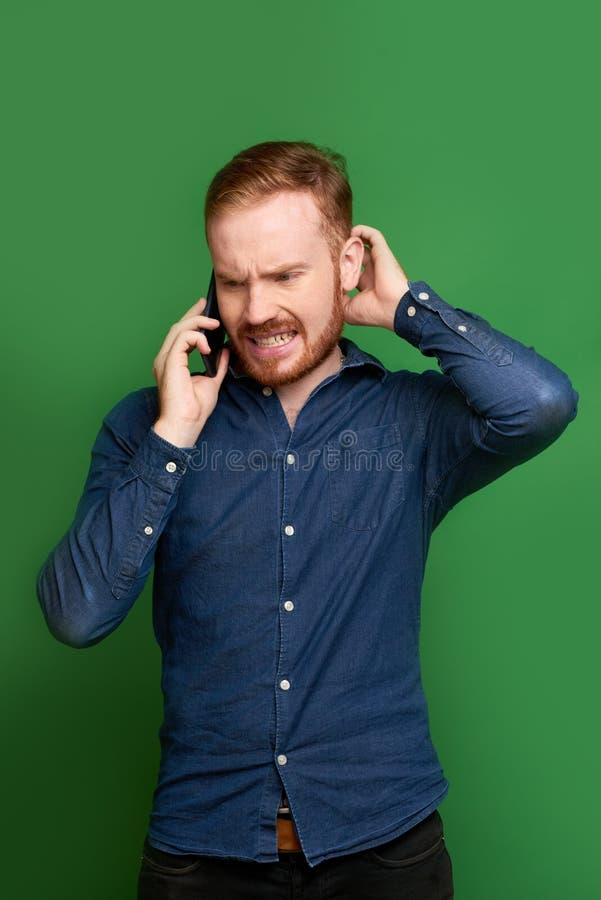 Hombre olvidadizo que habla en el teléfono imágenes de archivo libres de regalías