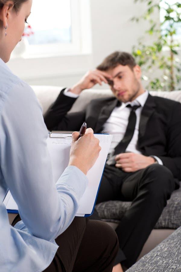 Hombre opreso que habla con el psicólogo imágenes de archivo libres de regalías