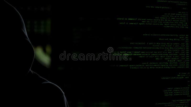 Hombre oscuro anónimo en fondo de los códigos que roba los datos personales, malware de lanzamiento fotos de archivo libres de regalías