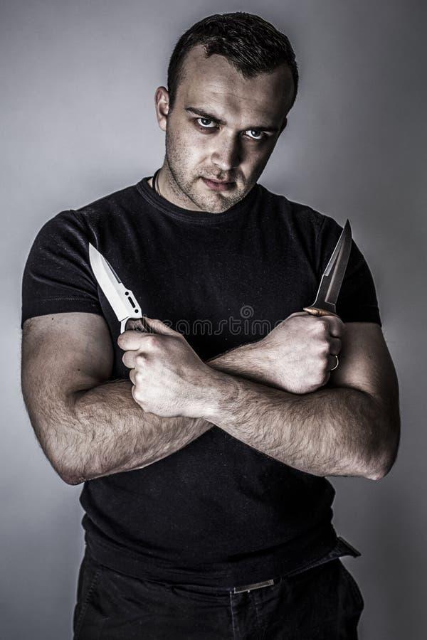 Hombre oscuro con dos cuchillos en sus manos imagenes de archivo