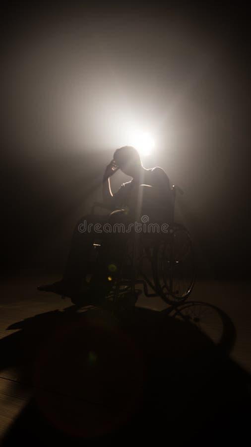 Hombre oscuro de la silueta en la silla de ruedas en la etapa del misterio la producción y la cinematografía video con la películ fotos de archivo libres de regalías