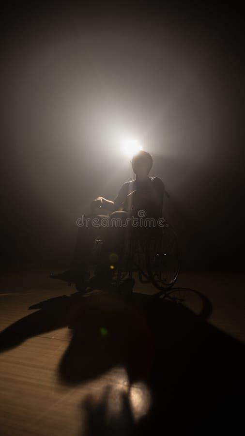 Hombre oscuro de la silueta en la silla de ruedas en la etapa del misterio la producción y la cinematografía video con la películ foto de archivo libre de regalías