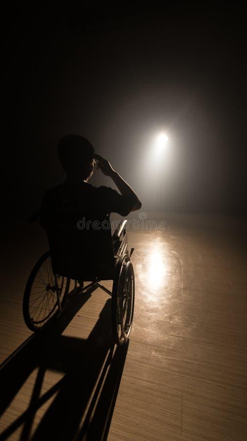 Hombre oscuro de la silueta en la silla de ruedas en la etapa del misterio varón adulto discapacitado que se sienta en sombra imagen de archivo libre de regalías