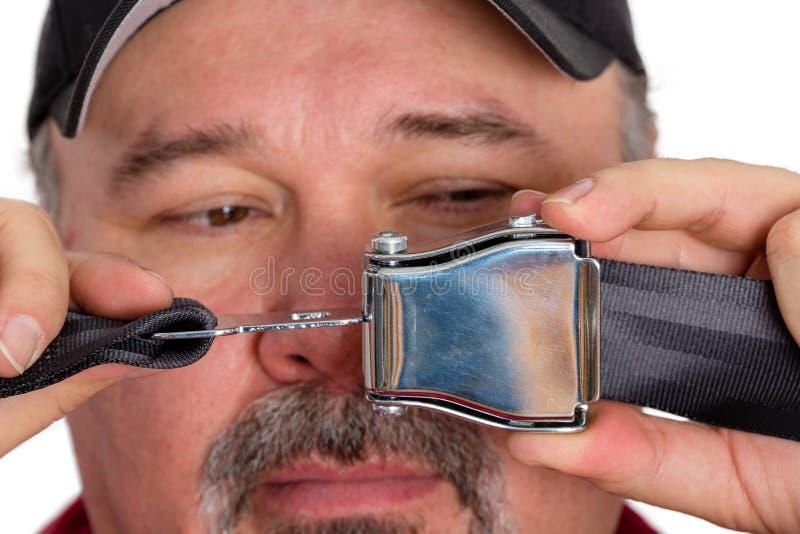 Hombre oscuro-ingenioso estúpido incapaz de sujetar un cinturón de seguridad imagen de archivo libre de regalías
