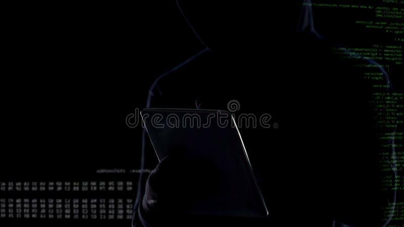 Hombre oscuro que mecanografía en la tableta, ataque ilegal en la privacidad, ciberdelincuencia foto de archivo libre de regalías