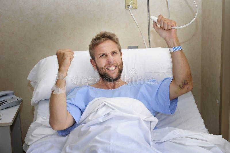 Hombre paciente enojado en el sitio de hospital que miente en la cama que presiona la sensación del botón de la llamada de la enf foto de archivo