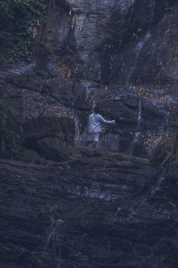HOMBRE PARADO EN LA ROCA Y VER LA CAÍDA DEL AGUA imagen de archivo