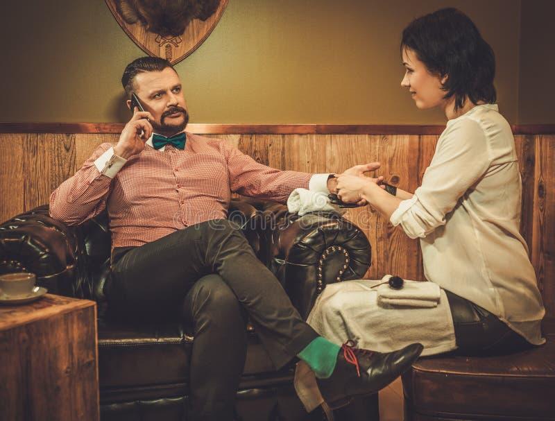 Hombre pasado de moda confiado que habla en el teléfono móvil y que hace la manicura masculina en una peluquería de caballeros imagenes de archivo