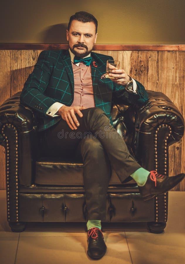 Hombre pasado de moda confiado que se sienta en silla de cuero cómoda con el vidrio de whisky en interior de madera en la peluque foto de archivo libre de regalías