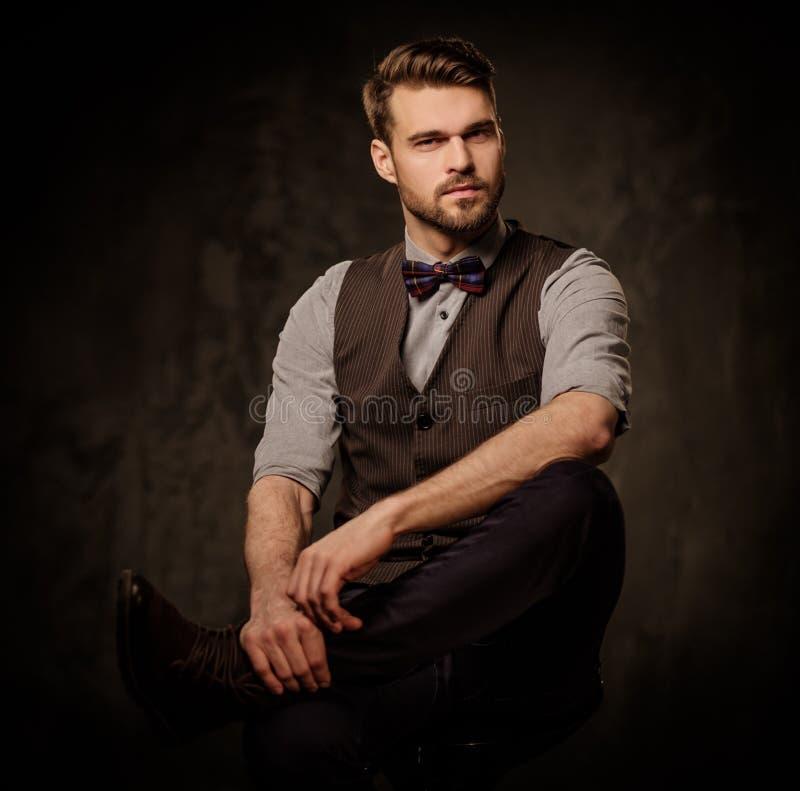 Hombre pasado de moda hermoso joven con la barba que presenta en fondo oscuro foto de archivo libre de regalías