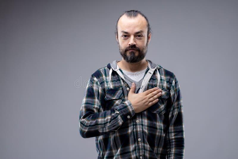Hombre patriótico o sincero que pone la mano en corazón fotos de archivo