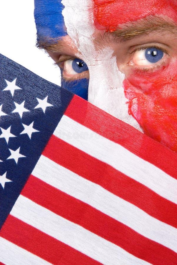 Hombre patriótico que mira con fijeza sobre un indicador americano imagen de archivo