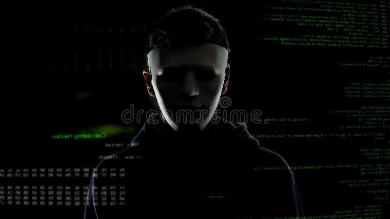 Hombre peligroso en la máscara blanca en el fondo de los códigos y de los números, cortando concepto foto de archivo libre de regalías