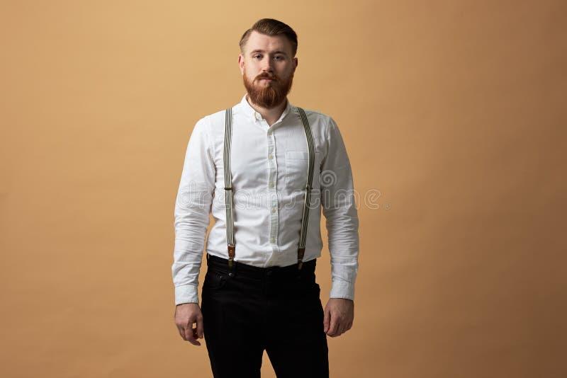 Hombre pelirrojo con la barba vestida en una camisa blanca y pantalones negros con los soportes de la liga en un fondo beige en imagen de archivo libre de regalías
