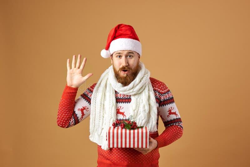 Hombre pelirrojo divertido con la barba vestida en un suéter rojo y blanco con los ciervos, una bufanda hecha punto blanca y un s imagen de archivo libre de regalías