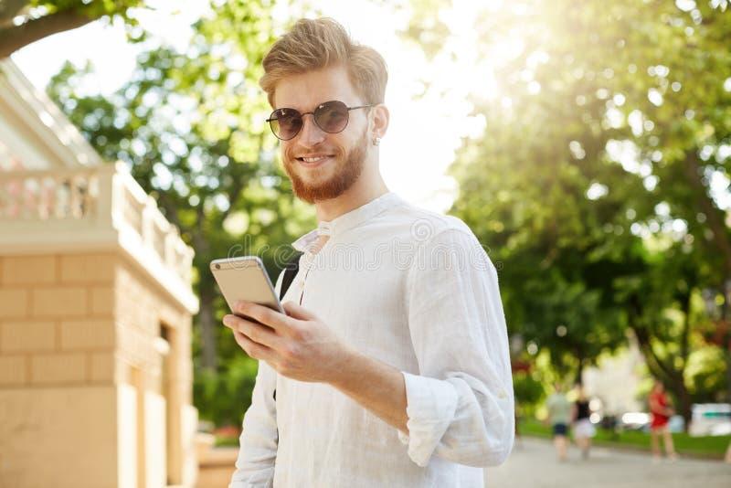 Hombre pelirrojo positivo y sonriente joven con la barba y pendiente en las gafas de sol que miran a través de redes sociales en  imagen de archivo libre de regalías